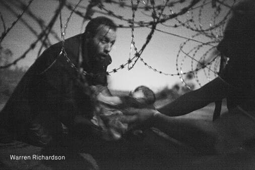A man passes a baby through the fence at the Serbia/Hungary border in Röszke, Hungary, 28 August 2015. / Warren Richardson, Australia, 2015, Hope for a New Life