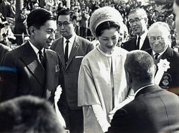 Close up of Crown Prince Akihito and Empress Michiko meeting representatives of teams during the Opening Ceremony of the 1964 Tokyo Paralympic Games. Paralympic founder Ludwig Guttmann is in the background. / Wikipedia